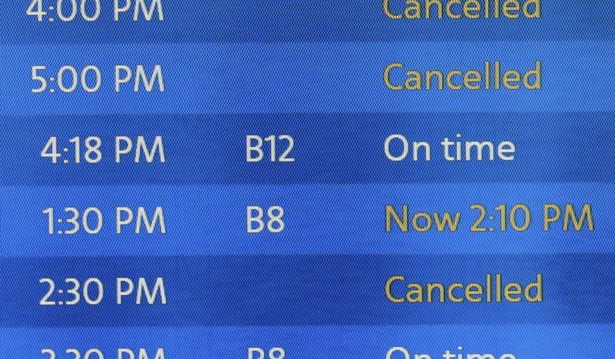 Flight cancelations are posted on a departure board for US Airways at Logan Airport in Boston, Monday, Jan. 26, 2015.  New England is bracing for a blockbuster blizzard threatening more than 2 feet of snow, hurricane-force winds, coastal flooding and widespread power outages. (AP Photo/Charles Krupa)