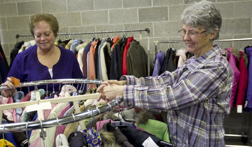 Andrea Schaab, right, and Sandy De Vormer, are pictured with Sitty's Wish clothing inside the Grand Rapids Public School's Facilities and Operations Department building Thursday, Jan. 22, 2015. Schaab, who volunteers with the 20-year-old charity that donates winter clothing for GRPS students, will be retiring after five years. (AP Photo/The Grand Rapids Press, Cory Morse)