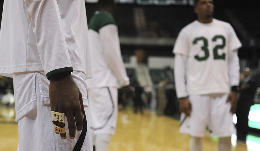 Tim Bond wears athletic tape bearing the number and initials of Shannise Heady before Eastern Michigan University's game against Ohio Tuesday, Jan. 27, 2015 at the Convocation Center in Ypsilanti, Mich. Shannise Heady, an Eastern Michigan University women's basketball player and another student were killed early Sunday when their car crossed the center line of a road and hit an oncoming vehicle, authorities say. (AP Photo/The Ann Arbor News, Alex McDougall) LOCAL TELEVISION OUT; LOCAL INTERNET OUT