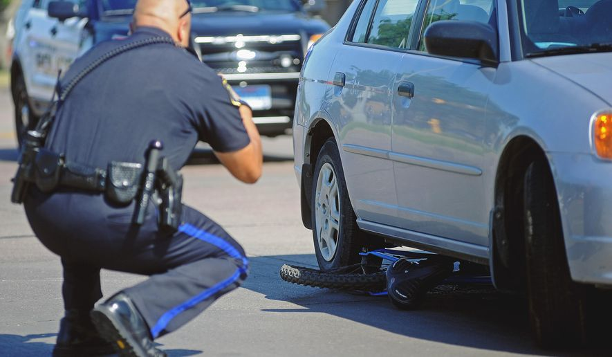 In this July 23, 2014 photo, a Sioux Falls police officer photographs a mangled bicycle underneath a car after a bicycle versus car accident in Sioux Falls, S.D. The South Dakota House Transportation Committee on Tuesday, Jan. 27, 2015, in Pierre, stalled for a second time in reaching a consensus on how to improve safety for cyclists when vehicles pass them on the road. From 2010 to 2013 in South Dakota, 390 cyclists were injured and three people died in collisions with vehicles. (AP Photo/Argus Leader, Joe Ahlquist )