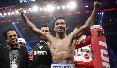 WBO welterweight champion Manny Pacquiao celebrates after defeating WBO junior welterweight champion Chris Algieri of the U.S.  during their welterweight title boxing match at the Venetian Macao in Macau, Sunday, Nov. 23, 2014. Pacquiao got the big knockdowns he desperately craved, battering Algieri around the ring Sunday on his way to a decision win in a lopsided welterweight title fight.(AP Photo/Kin Cheung)