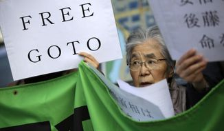 """A woman along with other protesters hold a placard and chant """"Free Goto"""" during a rally outside the prime minister's official residence in Tokyo, Tuesday, Jan. 27, 2015. A Japanese envoy in Jordan expressed hope that both a Japanese hostage and a Jordanian pilot held by Islamic militants will return home """"with a smile on their faces,"""" as criticisms mounted Tuesday over the government's handling of the crisis. (AP Photo/Eugene Hoshiko)"""