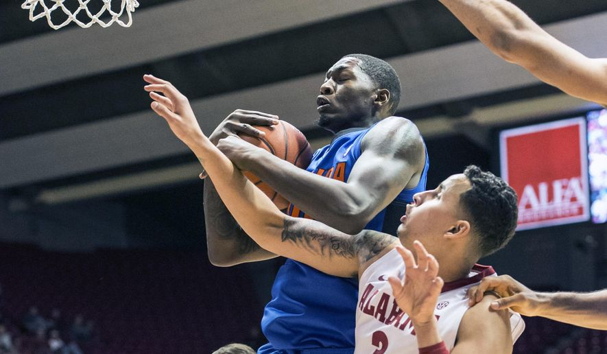Florida forward Dorian Finney-Smith (10) rebounds over Alabama forward Mike Kessens (3) during an NCAA college basketball game, Tuesday, Jan. 27, 2015, at Coleman Coliseum in Tuscaloosa, Ala. (AP Photo/AL.com, Vasha Hunt) MAGS OUT