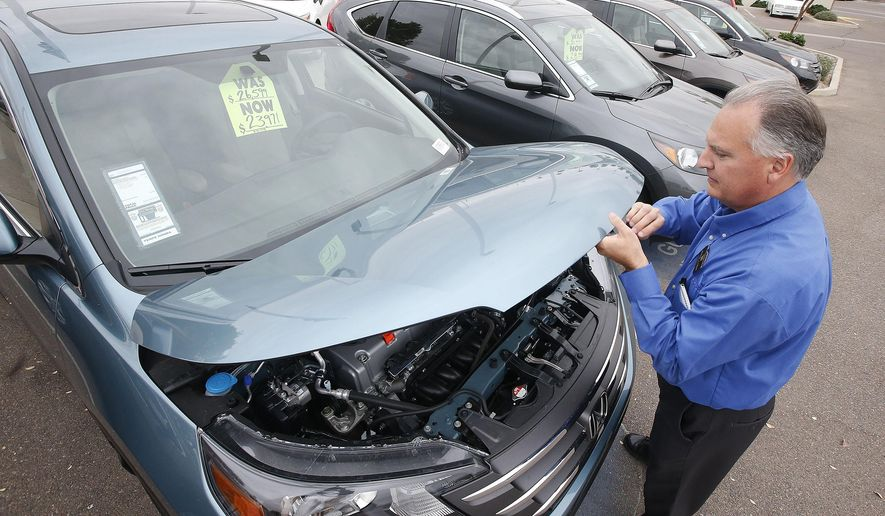 FILE - In this Dec. 2, 2014 file photo, Mike Johnson, a sales manager at a Honda car dealership, opens the hood of a Honda CRV SUV in Tempe, Ariz. The Commerce Department releases durable goods orders for January on Tuesday, Jan. 27, 2015. (AP Photo/Ross D. Franklin, File)