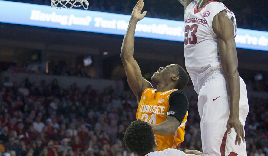 Tennessee forward Willie Carmichael III, center, shoots a layup as Arkansas forward Moses Kingsley, right attempts to block during the first half of an NCAA college basketball game on Tuesday, Jan. 27, 2015, in Fayetteville, Ark. AP Photo/Gareth Patterson)