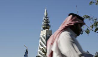 A Saudi man passes the al-Faisaliya tower in Riyadh, Saudi Arabia, Tuesday, Jan. 27, 2015. (AP Photo/Hasan Jamali) ** FILE **