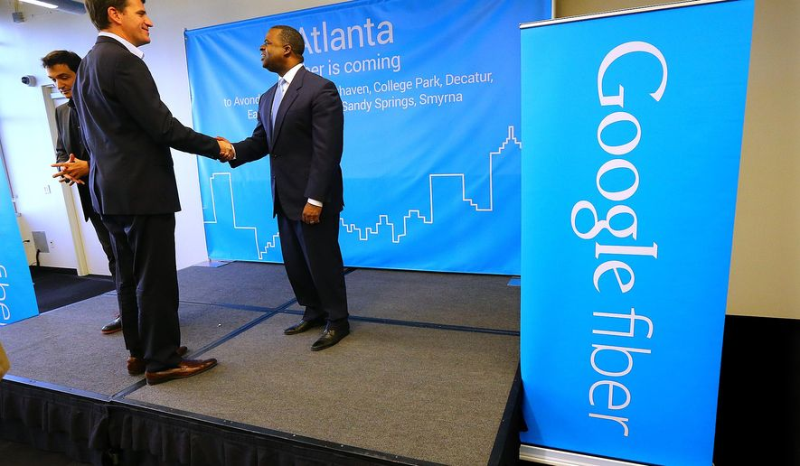 Tom Lowry, left, head of the Google Atlanta office, shakes hands with Atlanta Mayor Kasim Reed at the conclusion of a press conference announcing the launch of Google Fiber in Atlanta, one of four cities also including Charlotte, Raleigh-Durham, and Nashville on Tuesday, Jan. 27, 2015, in Atlanta.  (AP Photo/Atlanta Journal-Constitution, Curtis Compton)  MARIETTA DAILY OUT; GWINNETT DAILY POST OUT; LOCAL TELEVISION OUT; WXIA-TV OUT; WGCL-TV OUT