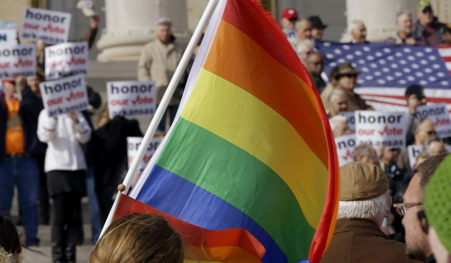 FILE- In this Nov. 19, 2014, file photo, supporters of Arkansas' law banning same sex marriage, top, hold a rally as a protestor waves a rainbow flag at the Arkansas state Capitol in Little Rock, Ark. A federal appeals court on Monday, Jan. 26, 2015, threatened to dismiss Arkansas' attempt to restore a gay marriage ban after state lawyers failed to pay a $505 docketing fee that came due as the state changed attorneys general. (AP Photo/Danny Johnston, File)