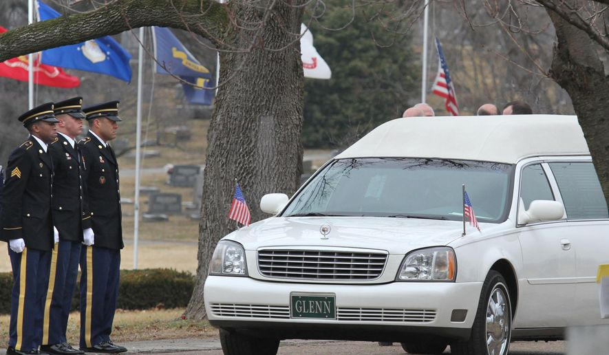 Kentucky National Guard members stand at attention as the hearse carrying the remains of former U.S. Sen. Wendell Ford arrives at Elmwood Cemetery, Tuesday, Jan. 27, 2015, in Owensboro, Ky. Ford, a former Kentucky governor, was remembered at his service by Vice President Joe Biden and former President Bill Clinton. (AP Photo/The Messenger-Inquirer, Greg Eans)