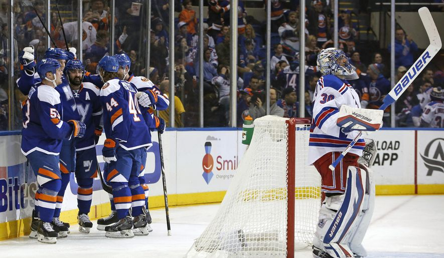 New York Islanders teammates celebrate with left wing Matt Martin, second from left, behind the net as New York Rangers goalie Henrik Lundqvist (30) of Sweden looks up to a replay on the video screen in the second period of an NHL hockey game in Uniondale, Tuesday, Jan. 27, 2015. It was the second goal of the game. (AP Photo/Kathy Willens)