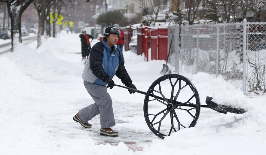 A man uses a shovel with a wheel to clean out a sidewalk following an overnight snowstorm, Tuesday, Jan. 27, 2015, in Jersey City, N.J.   A storm packing blizzard conditions spun up the East Coast early Tuesday, pounding coastal eastern Long Island into Maine with high winds and heavy snow. (AP Photo/Julio Cortez)