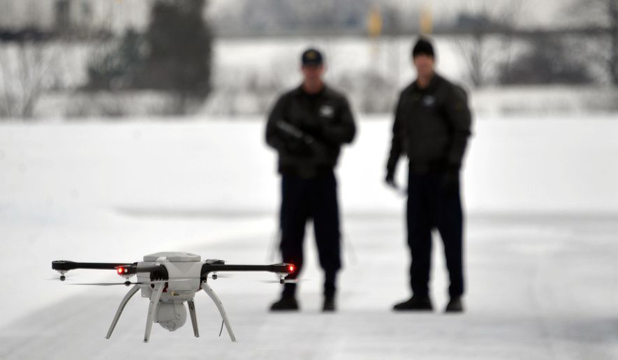 Michigan State Police Sgt. Matt Rogers and Trooper Don Zinz bring the Aeryon SkyRanger in for a landing during a demonstration of the MSP's new Unmanned Aircraft System (UAS), Jan. 15, 2015 at the State Police training track in Dimondale, Mich. Michigan State Police have asked for authorization to use an aerial drone to photograph vehicle crash scenes and give a bird's-eye view of other emergency situations across the state. (AP Photo/Detroit News, Dale G. Young)  DETROIT FREE PRESS OUT; HUFFINGTON POST OUT