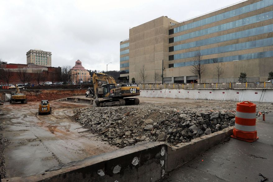 In this Jan. 26, 2015 photo, heavy machinery nears completion of the removal of a 1960s-era parking garage in downtown Asheville, N.C. A developer will begin constructing a nine-story, upscale hotel with retail along the street _ circling back to what was there before the '60s. Communities across the country are demolishing the garages and putting up buildings again, confident that more people will be drawn to lively offices, hotels and housing. (AP Photo/The Citizen-Times, William Woody)