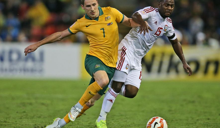 Australia's Mathew Leckie, left, and UAE's Ismail al Hammadi battle for the ball during the AFC Asian Cup semifinal soccer match between Australia and United Arab Emirates in Newcastle, Australia, Tuesday, Jan. 27, 2015. (AP Photo/Rick Rycroft)