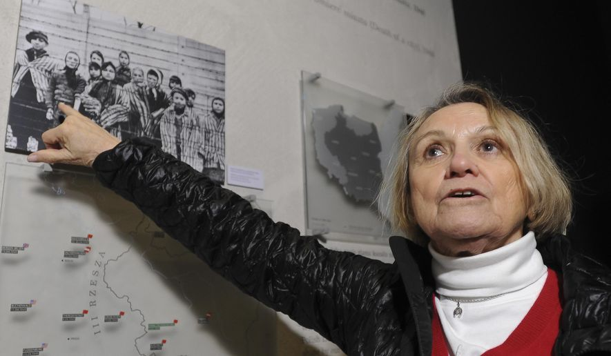 In this Saturday, Jan. 24, 2015 photo Paula Lebovics, an 81-year-old Holocaust survivor points to a photo showing herself as a child and other children at the Auschwitz-Birkenau Nazi death camp pictured after the camp was liberated by the Soviet Red Army, at the POLIN Museum of the History of Polish Jews, in Warsaw. Lebovics was 11 at that time. (AP Photo/Alik Keplicz)