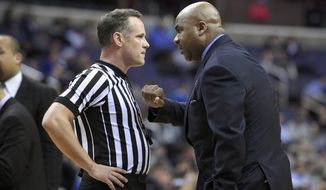 Georgetown head coach John Thompson III, right, talks with an official during a break in the action during the second half of an NCAA college basketball game against Xavier, Tuesday, Jan. 27, 2015, in Washington. Xavier won 66-53. (AP Photo/Nick Wass)