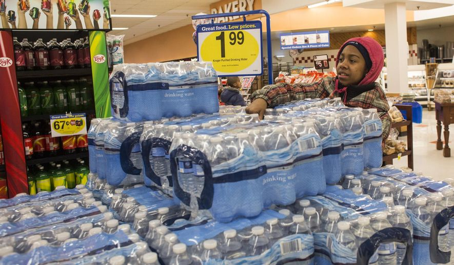 Flint resident Miesha Woodley, 13, grabs a case of water in Kroger, Wednesday, Jan. 28, 2015, in Flint, Mich. Mott Community College officials said they will continue doing their own water testing as Flint deals with fixing its drinking water distribution and treatment systems. (AP Photo/The Flint Journal, Erin Kirkland) LOCAL TV OUT; LOCAL INTERNET OUT