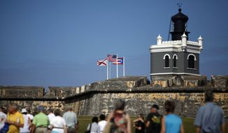 "SAN JUAN P.R. -Tourists walk near the 16th century Spanish fort called El Morro in Old San Juan, Puerto Rico. There's an entrance fee to enter the Castillo San Felipe del Morro, but the best way to enjoy this U.S. National Historic Site requires no money at all. The fort that towers over San Juan Bay, known universally as just ""El Morro,"" is a great place to stroll, especially at sunset. The massive rolling expanse of grass at the foot of the fort has spectacular views in any direction. It's a popular place to picnic and fly a kite, sold by nearby street vendors. (AP Photo/Ricardo Arduengo, File)"