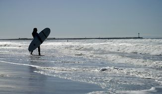 SAN DIEGO, CA -Harmony Lallo, visiting from Franktown, Colo., tries her hand at surfing under mostly sunny skies Wednesday, Nov. 12, 2014, in San Diego, as her home state was pummeled with snow. A blast of arctic air is blanketing the country's mid-section this week, while Southern California enjoys ample sunshine. (AP Photo/Gregory Bull)