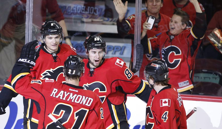 Calgary Flames' Josh Jooris, center, celebrates his game-winning goal against the Buffalo Sabres with teammates Joe Colborne, Mason Raymond and Kris Russell, from left, during the third period of an NHL hockey game Tuesday, Jan. 27, 2015 in Calgary, Alberta. (AP Photo/The Canadian Press, Larry MacDougal)