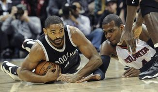 Brooklyn Nets guard Alan Anderson, left, and Atlanta Hawks forward Paul Millsap, right, vie for a loose ball during the first half of an NBA basketball game, Wednesday Jan. 28, 2015, in Atlanta. (AP Photo/John Amis)