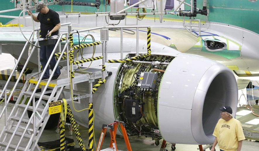 In this Dec. 16, 2014 photo, workers walk near an engine of a Boeing 737-800 airplane being assembled at Boeing's 737 facility in Renton, Wash. Boeing reports quarterly financial results on Wednesday, Jan. 28, 2015. (AP Photo/Ted S. Warren)