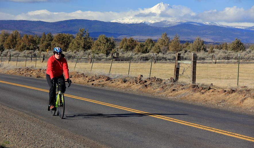 David Davis rides the Madras Mountain Views Scenic Bikeway, a 30 mile route in Central Oregon, which offers views of Mount Jefferson and other Cascade Mountain peaks on Jan. 19, 2015 in Central Oregon.  While it does offer a higher percentage of sunshine-filled days, a freezing fog sometimes invades the valley. If the weather isn't clear and sunny, it's probably not worth getting on your bicycle.  (AP Photo/Statesman-Journal, Zach Urness  )