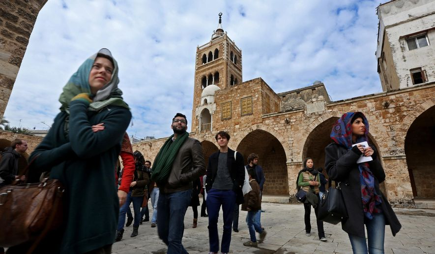 In this Saturday, Jan. 17, 2015 photo, tourists visit the Mamulk-era Great Mosque, during a day trip in the northern city of Tripoli, Lebanon. As the tour group made its way through the narrow alleys of the seaside city of Tripoli, marveling at its medieval architecture, residents stared back at a sight that for them was just as exotic - visitors in their poor, restive corner of Lebanon. (AP Photo/Bilal Hussein)