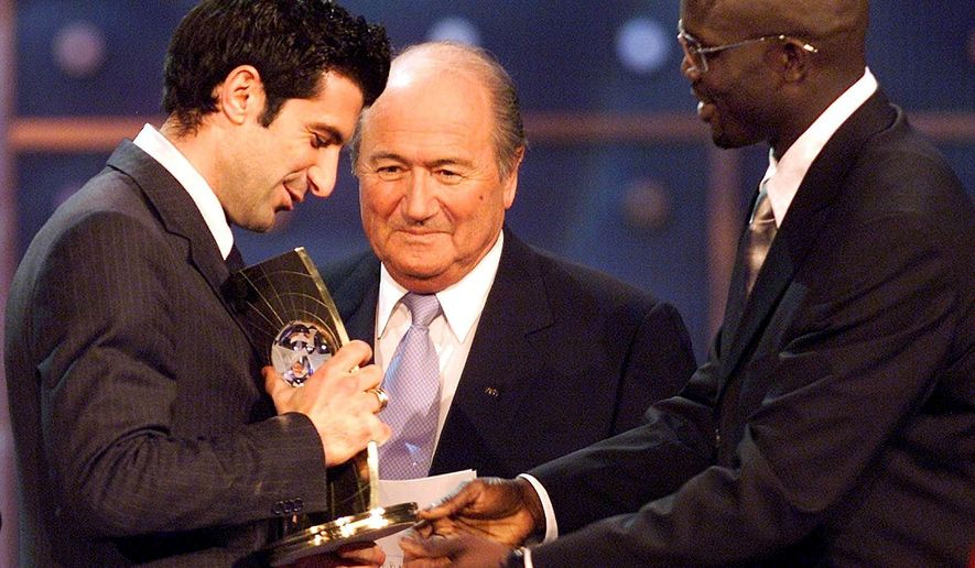 "FILE - In this Monday, Dec. 17, 2001 file photo, Portuguese player Luis Figo, left, of Spanish team Real Madrid receives his trophy as FIFA ""World Player of The Year 2001"" from Swiss FIFA president Joseph Blatter, center, and Georges Weah of Liberia, right, during the awards ceremony of the FIFA trophies in Zurich, Switzerland. Luis Figo said in an interview on Tuesday, Jan. 27, 2015 that he wants to become FIFA president and has the nominations needed to be an official candidate against Sepp Blatter. (AP Photo/Keystone, Michele Limina, File)"