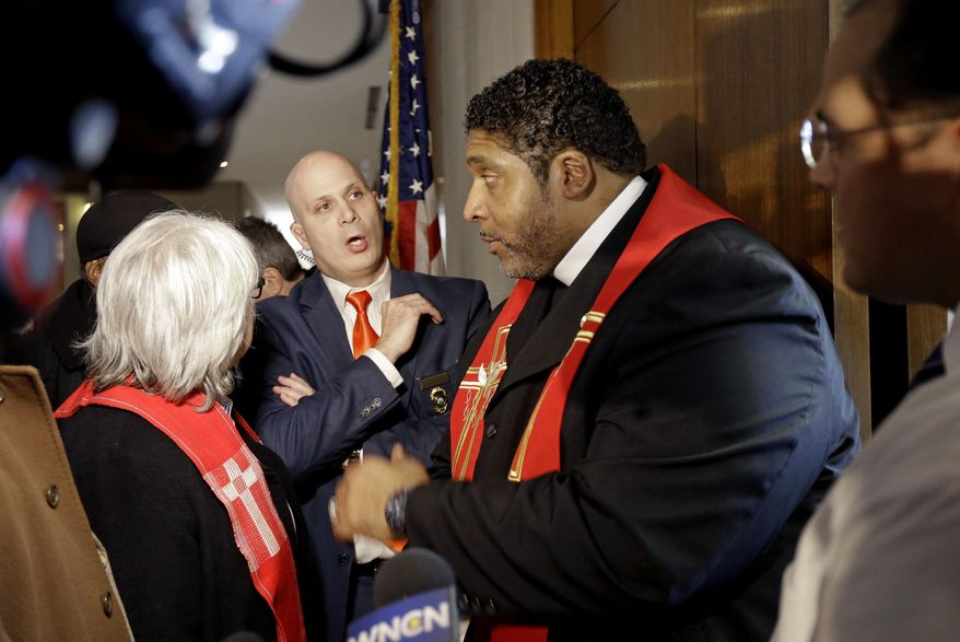Rev. William Barber, right, President of the North Carolina chapter of the NAACP, speaks with General Assembly Police Lt. Martin Brock, facing, while attempting to enter House Speaker Tim Moore's office at the Legislative building in Raleigh, N.C., Wednesday, Jan. 28, 2015. Religious leaders hand-delivered their moral agenda to representatives' offices Wednesday.  North Carolina's NAACP leader challenged new rules concerning public assembly in the State Legislative Building as part of protests on Wednesday targeting legislative policies by GOP leaders who control both chambers. (AP Photo/Gerry Broome)