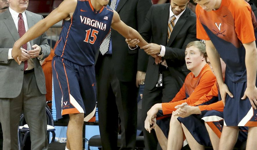 FILE - In this Jan. 17, 2015, file photo, Virginia guard Malcolm Brogdon (15) is congratulated by the bench after coming out of the game late in the second half of their 66-51 win over Boston College in an NCAA college basketball game in Boston. Brogdon is rarely the guy that winds up on the highlight shows, but as No. 2 Virginia rolls along at 19-0, the player his teammates call Uncle Malcolm is usually right in the middle of all they do. (AP Photo/Mary Schwalm, File)