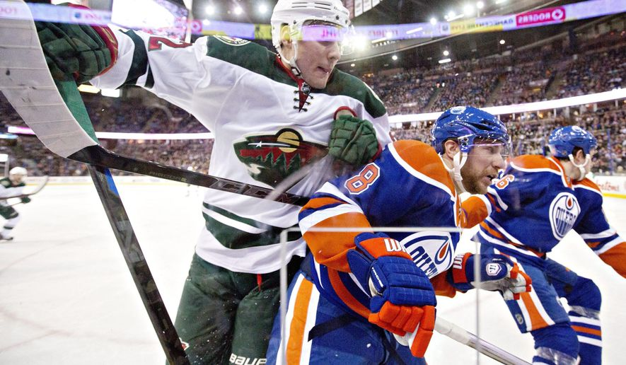 Minnesota Wild's Nino Niederreiter (22) checks Edmonton Oilers' Derek Roy (8) during first period NHL hockey action in Edmonton, Alberta, on Tuesday Jan. 27, 2015. (AP Photo/The Canadian Press, Jason Franson)