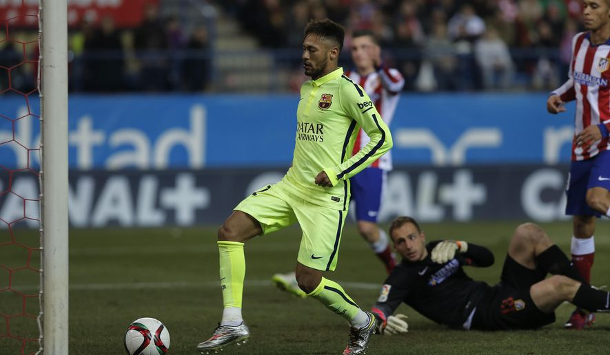 Barcelona's Neymar, left, scores his second goal during a second leg quarterfinal Copa del Rey soccer match between Atletico de Madrid and FC Barcelona at the Vicente Calderon stadium in Madrid, Spain, Wednesday, Jan. 28, 2015. (AP Photo/Andres Kudacki)