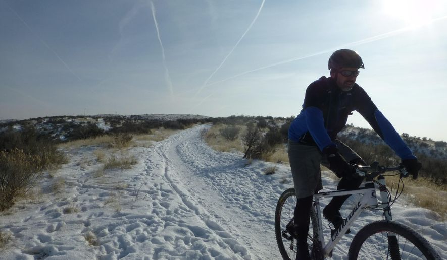 Roger Phillips rides down a snowy trail near Eagle, Idaho, Jan. 2, 2014, in this self portrait.   Regular mountain bikes can be ridden on trails with hard-packed snow. Dropping tire pressure by about 5 pounds improves traction. (AP Photo/Idaho Statesman, Roger Phillips)