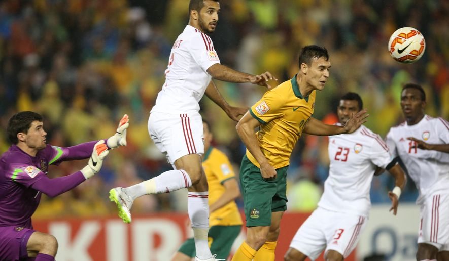 UAE's Ali Ahmed Mabkhout, center, battle for the ball against Australia's Trent Sainsbury, right, and Mathew Ryan, left, during the AFC Asian Cup semifinal soccer match between Australia and United Arab Emirates in Newcastle, Australia, Tuesday, Jan. 27, 2015. (AP Photo/Rick Rycroft)