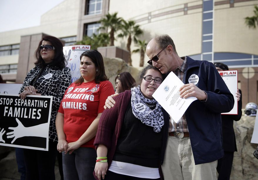 Bob Fulkerson, right, embraces Dulce Valencia during a protest Wednesday, Jan. 28, 2015, in Las Vegas. They are part of a group that was demanding that Nevada Attorney General Adam Laxalt drop a lawsuit against President Barack Obama's immigration action. (AP Photo/John Locher)