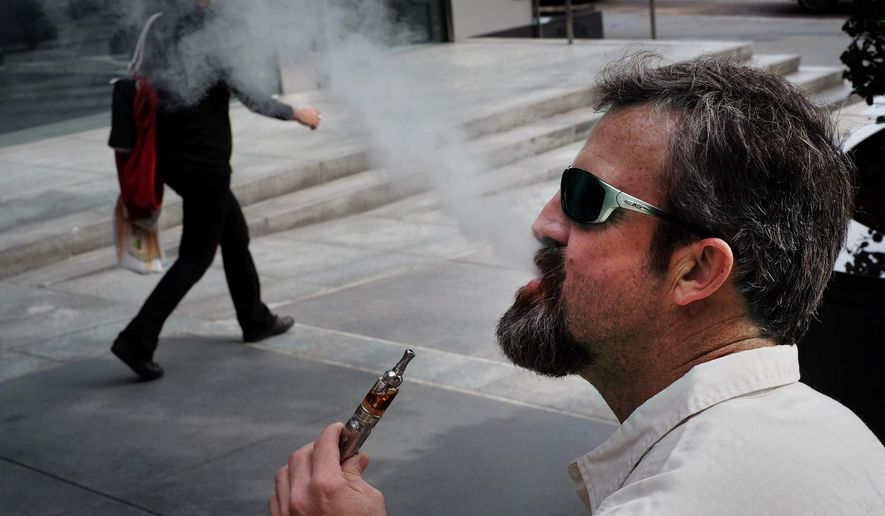 "Paul Frohman smokes an electronic cigarette outside an office building in downtown Los Angeles on Wednesday, Jan. 28, 2015. California health officials  declared electronic cigarettes a health threat that should be strictly regulated like tobacco products, joining other states and health advocates across the U.S. in seeking tighter controls as ""vaping"" grows in popularity. (AP Photo/Richard Vogel)"
