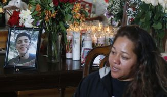 Laura Hernandez talks with reporters in her Thornton, Colo., home on Wednesday, Jan. 28, 2015, about the death of her 17-year-old daughter Jessica, who was killed after she allegedly hit and injured a Denver Police Department officer while driving a stolen vehicle early Monday in northeast Denver alleyway. Photographs of Jessica Hernandez stand on a table covered with bouquets of flowers and a display of candles at back in the family's home. (AP Photo/David Zalubowski)