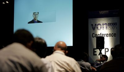 Participants listen to Niklas Zennstrom, founder & CEO of Skype,  on the screen, talking on the phone  during an Internet phone technology show regarding industry perspective, at Boston Convention and Exhibition Center, Tuesday, Sept. 20 , 2005.   (AP Photo/Chitose Suzuki)