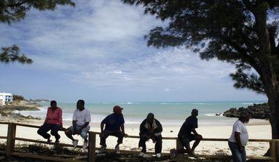 BERMUDA -Local islanders sit on a wall at John Smith's Bay in Smith's Parish following Hurricane Igor in Bermuda, Monday, Sept. 20, 2010. (AP Photo/Gerry Broome)