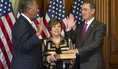 House Speaker John Boehner of Ohio administers a ceremonial re-enactment of the oath-of-office to Rep. Blaine Luetkemeyer, R-Mo., accompanied by his wife Jackie, Tuesday, Jan. 6, 2015, on Capitol Hill in Washington. (AP Photo/Cliff Owen)