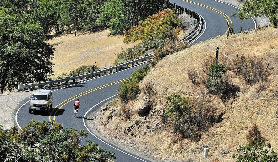 This photo from May, 2014 shows a Cycle Oregon Rider riding down Dead Indian Memorial Road near Ashland, Ore. (AP Photo/The Medford Mail Tribune, Jamie Lusch)