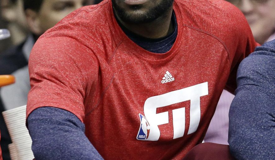 Cleveland Cavaliers' LeBron James watches from the bench as the Cavaliers play the Portland Trail Blazers during an NBA basketball game Wednesday, Jan. 28, 2015, in Cleveland. (AP Photo/Tony Dejak)