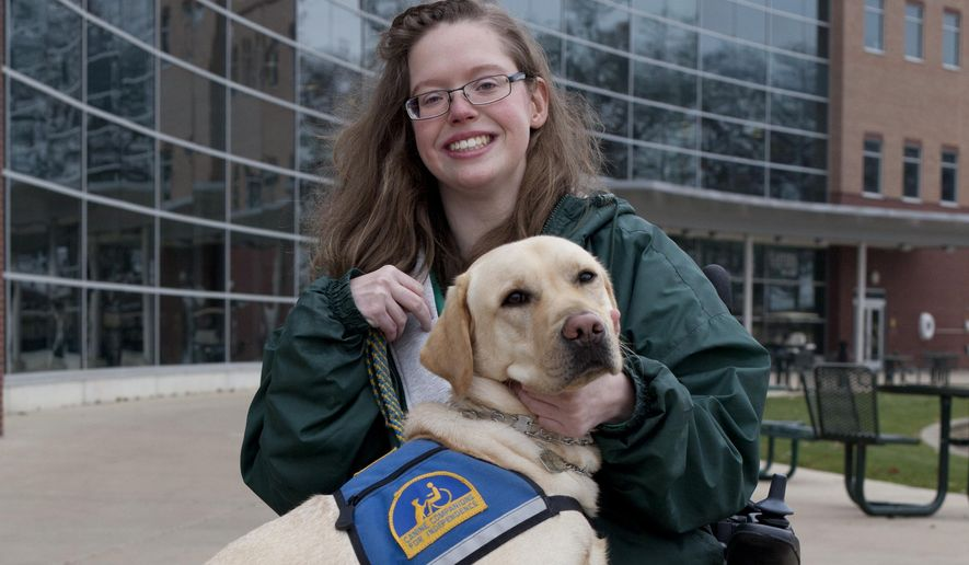 Eastern Michigan University student Courtney Bailey poses for a picture with her assistance dog, Rolo, outside the Student Center on campus in Ypsilanti, Mich., on Dec. 5, 2014.  Bailey has Cerebral Palsy and Rolo helps with everyday tasks. (AP Photo/The Ann Arbor News, Patrick Record)