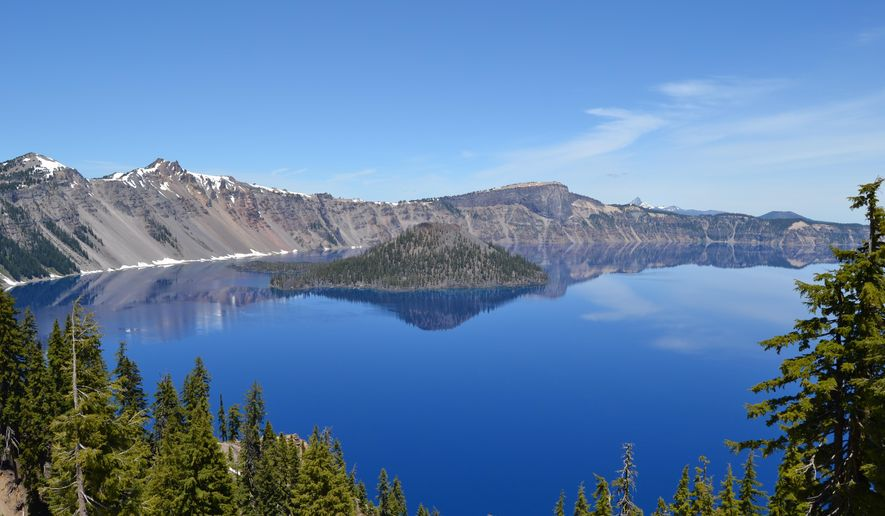FILE - In this undated file photo, Wizard Island is seen in this scenic view from the lodge area at Crater Lake National Park about 90 miles south of Bend, Ore. Trip visits to the lake, along with other Oregon areas such as John Day Fossil Bed National Monument and Smith Rock State Park, surged in 2014 as part of a $2.3 million Seven Wonders campaign by Wieden+Kennedy ad agency.(AP Photo/Statesman-Journal, Alisha Roemeling, file)