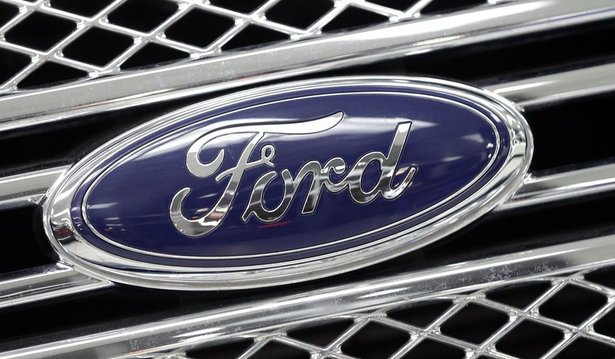 In this photo taken Monday, Jan. 5, 2015, the Ford logo shines on the front grille of a 2014 Ford F-150, on display at a local dealership in Hialeah, Fla. Ford's net income tumbled in the fourth quarter as the company took an expected charge to deal with currency devaluation at its Venezuelan operations, the company announced, Thursday, Jan. 29, 2015. But without that loss and other one-time items, Ford came out ahead of Wall Street's expectations for the fourth quarter and the full year. (AP Photo/Alan Diaz)
