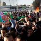 Pro-Gadhafi supporters chant in support of the Libyan Leader at the scene of a fuel-tanker explosion, which security forces at the scene said was due to a road accident, in Tripoli, Libya Wednesday, March 2, 2011. (AP Photo/Ben Curtis) (credit)