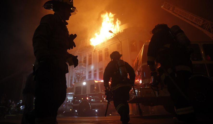 San Francisco Fire Department members fight a four-alarm fire at 22nd and Mission Street in San Francisco, Calif., on Wednesday, Jan. 28, 2015. Fire officials say one person is dead and at least four people have been injured in the massive, four-alarm fire in San Francisco's Mission District. (AP Photo/San Francisco Chronicle, Scott Strazzante)