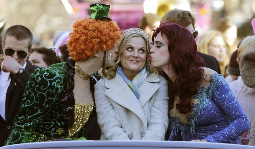 """Actress Amy Poehler, center, is kissed by Jason Hellerstein, left, and Sam Clark, who are dressed in drag, as she rides in a convertible through Harvard Square in Cambridge, Mass., Thursday Jan. 29, 2015. Poehler was honored as """"Woman of the Year"""" by the Hasty Pudding Theatricals at Harvard University. (AP Photo/Charles Krupa)"""