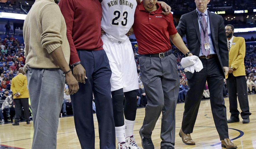 New Orleans Pelicans forward Anthony Davis (23) is helped off the court after pulling his groin during the second half of an NBA basketball game against the Denver Nuggets in New Orleans, Wednesday, Jan. 28, 2015. The Nuggets won 93-85. (AP Photo/Gerald Herbert)